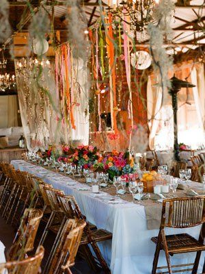 I think it would be gorgeous to have flowers, lights and ribbons dangling above the tables (: