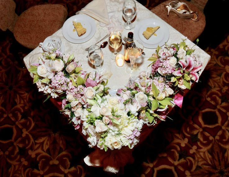 An overhead view of the beautiful bridal party bouquets on the sweetheart table at Harry's Savoy Ballroom.