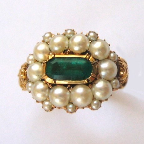 A Regency pearl & emerald cluster ring with ornate gold scrollwork shoulders, the rub-over set elongated oval emerald measuring approximately 7 x 3.5mm horizonatelly aligned and surrounded by ten natural pearls measuring approx.  3mm in diameter, with a seed pearl set inbetween each one, all cutdown collet-set in yellow gold with a closed back to the settings, to a tapered yellow gold shank with ornately-carved floral & scroll motifs, engraved LF & HW,  circa 1810