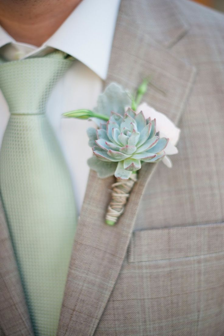 The groom will wear a grey succulent, white ranunculus, and dusty miller boutonniere.