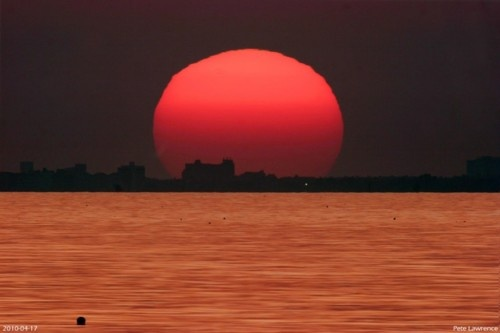 On April 17, 2010 the sky was clear and the Sun's colour was spectacular as night approached. This striking telescopic view even captures the Sun's swollen and distorted shape from the southern coast of the UK. Reflecting a bright column of sunlight, the sea also appears golden, with the horizon marked by the city of Portsmouth.