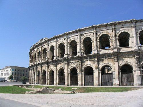 АМФИТЕАТР (греч.) [amphitheatre; Amphitheater n; amphithéâtre (m)] — грандиозное монументальное сооружение Древнего Рима, где проводились бои гладиаторов, театральные представления. План амфитеатра представлял собой эллипс, в середине его находилась огромная арена, вокруг которой возвышавшимися уступами размещались места для зрителей. В настоящее время амфитеатром называются места в театре, расположенные повышающимися рядами за партером.  Примеры амфитеатров:   Амфитеатр в Ниме (Франция)