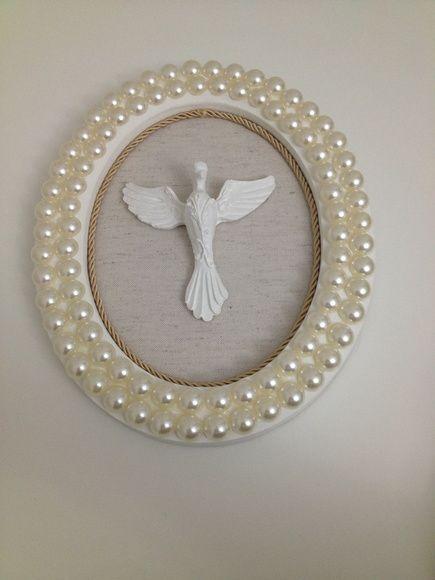 Quadro decorativo, confeccionado em MDF, moldura oval, fundo em tecido, imagem em resina divino espirito santo e acabamento em cordão e perolas.  *Produto artesanal sujeito a pequenas variações*