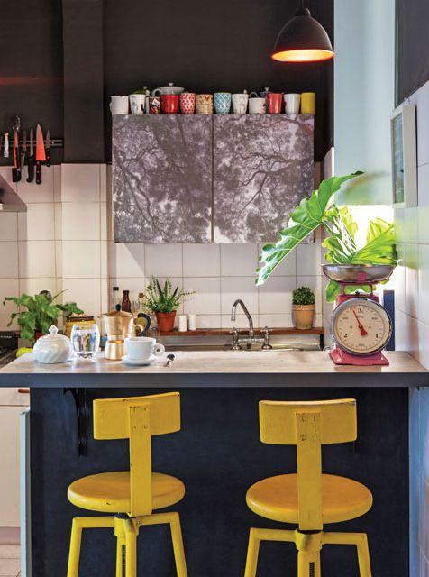 La cocina de este departamento está revestida en azulejos blancos y tiene una barra de melamina con tapa de paraíso, banquetas recicladas y una lámpara industrial metálica.