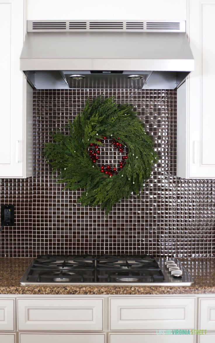 Faux Cedar Wreath Hanging Over Stove On Backsplash In A Christmas Kitchen.  #christmasdecor #