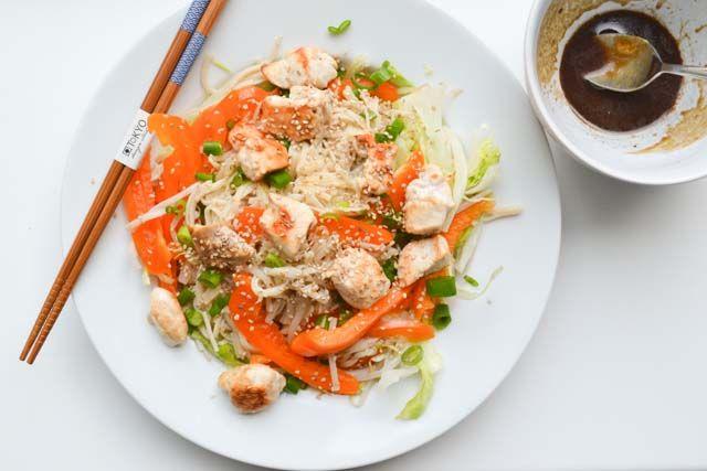 Een gezonde en knapperige Aziatische Kip salade met bruine rijstnoedels, met een gepaste oosters smakende dressing en sesamzaadjes.