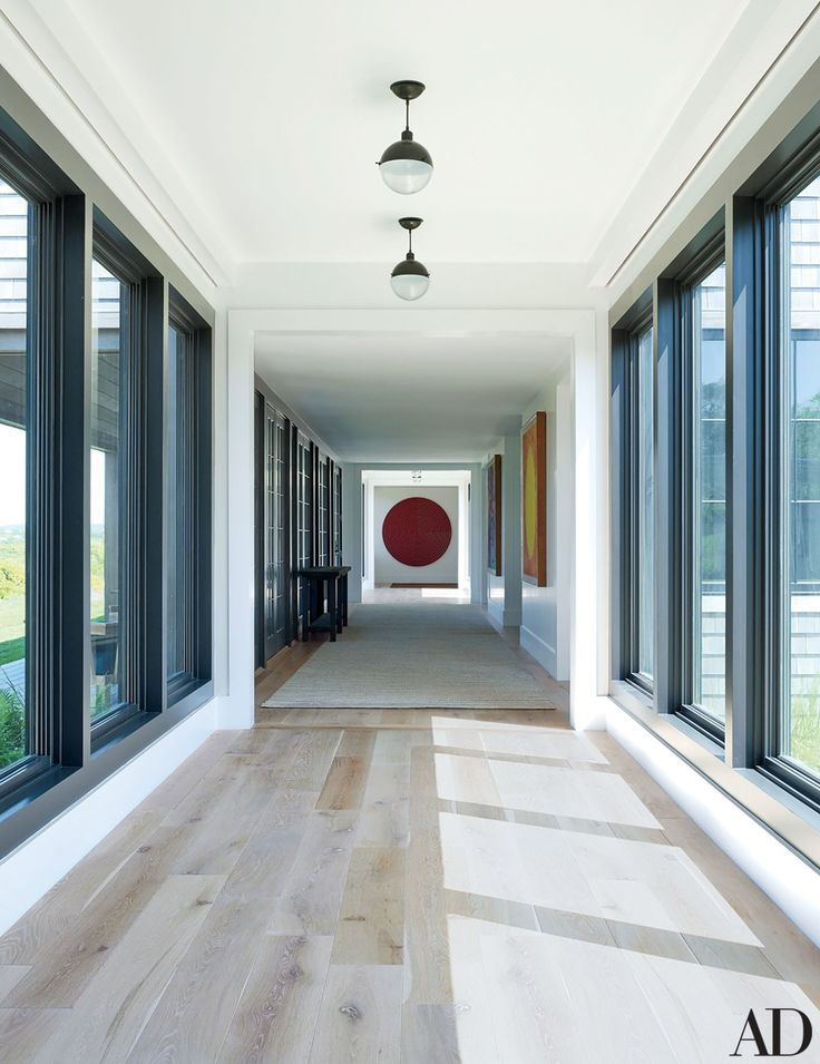 Pendant lamps from Obsolete punctuate the corridor that leads to the guest wing; the circular painting is by Ned Vena.