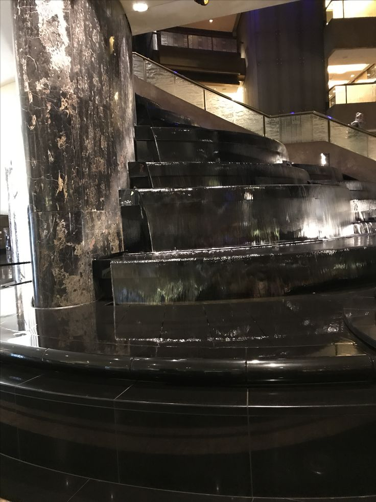 Photo 9: Marble water feature at Crown. This Black Marble water feature is a step like style, with each step being rounded helps draw your eye towards the upstairs space.