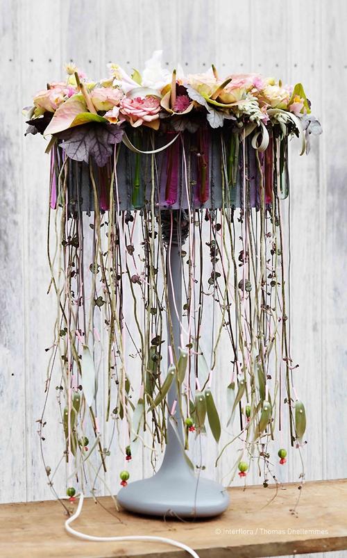"""Gil Boyard répare et embellit les """"lampes suédoises"""". A l'aide de scoubidous, d'épingles, de pipettes, il crée un abat-jour de roses thé, mini anthuriums, edelweiss, craspedias, immortelles roses, tillandsias xerographicas, heuchères, ceropegias, argenteums, diplocyclos et racine de vandas. Création florale extraite du Carnet d'Idées #Interflora ! #artfloral #fleurs"""