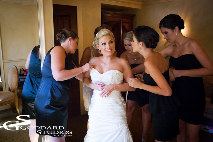 """As her bridesmaids are busy fixing her dress, the bride looks happily away, in anticipation of her """"first look""""."""