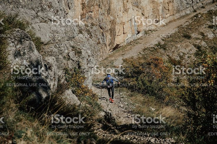 Yalta, Russia - October 6, 2016: young male athlete with walking poles to walk uphill on background sheer cliff during Crimea mountain marathon