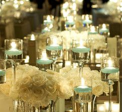 Floating Candle Holders w/ Long Stems. Love the white flowers and colored floating candles. Beautiful and classy