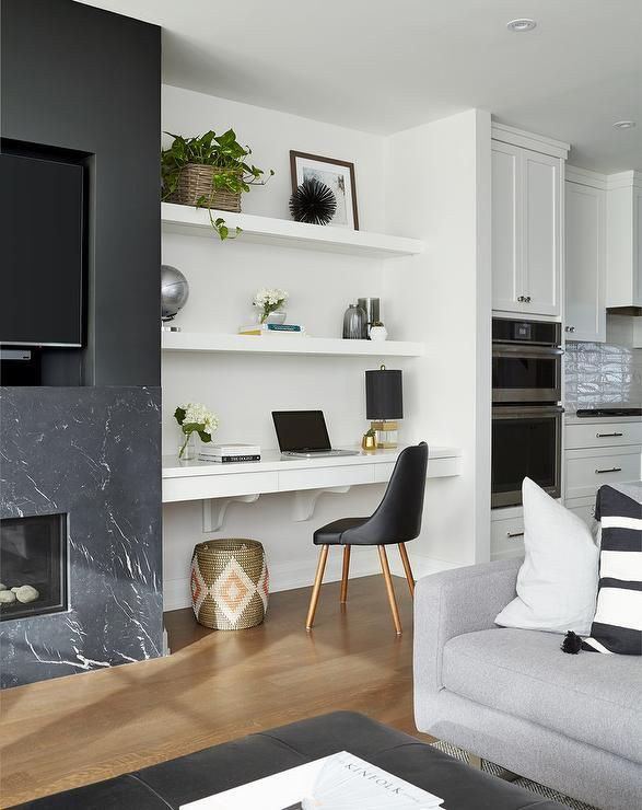 A Black Leather Desk Chair Sits At A White Built In Desk Positioned Beneath Stack Desk In Living Room Floating Shelves Living Room Built In Shelves Living Room