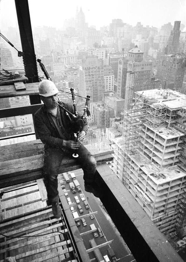 Construction worker playing a bagpipe in an unfinished building, 1957 by Arthur Rothstein
