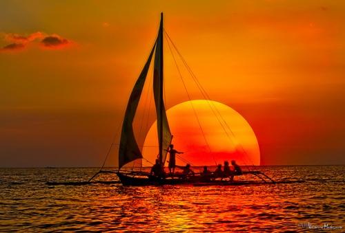 sinking sun, sailing ship