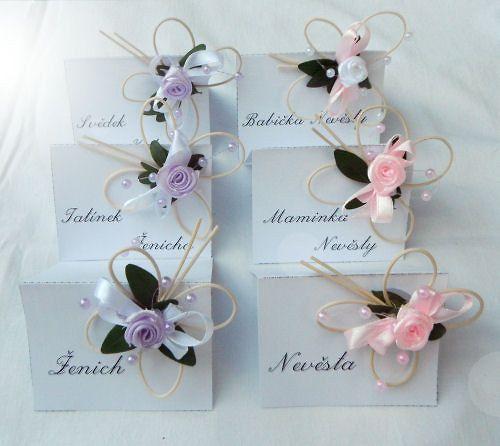 Svatební jmenovky - růžová-fialová Svatební jmenovky s látkovou růžičkou a perličkami dozdobí Váš svatební stůl.Vyrobeny z výkresového papíru. Po domluvě je možné objednat i v jiné barvě. Výška 5cm délka 7cm Cena za 1 ks Za příplatek 2,- Kč/ks zajistíme tisk nebo ruční napsání dle Vašeho seznamu.