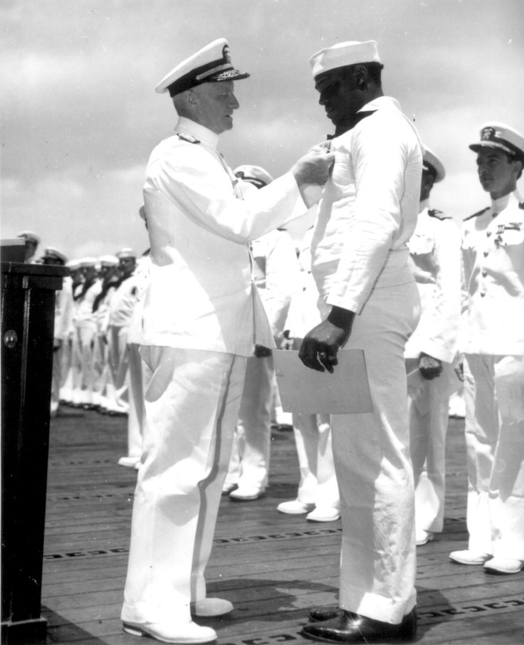 Chester W. Nimitz pins the Navy Cross on Doris Miller, at ceremony on board USS Enterprise (CV-6) at Pearl Harbor, May 27, 1942.