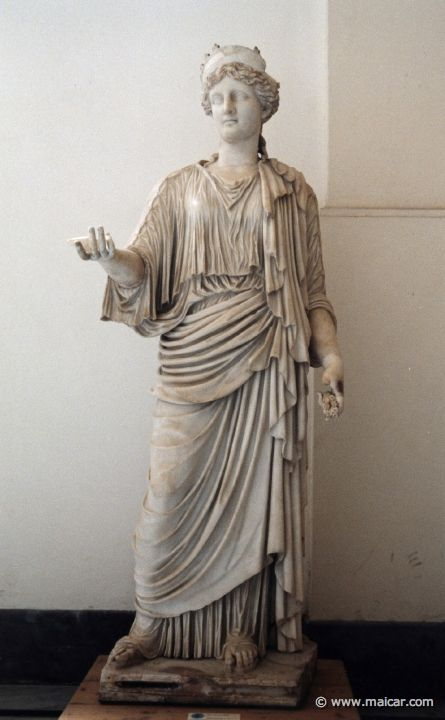 Nemesis, Roman copy from circa 430 CE, at the National Archaeological Museum, Naples. A goddess of divine retribution, she is seen here claiming back her dues. Deeply dislikes absence of moderation. Zealous in re-establishing order and proportion. She is sometimes with or without wings and sometimes crowned with stags and Nikes; her symbols are: apple blossoms, reins, lashes, swords, scales, the rudder, and a wheel.