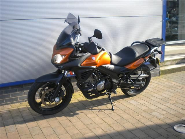 Suzuki V Strom DL 650   Fox Metallic Orange  1. MRA German touring screen  2. Suzuki hand guards  3. Oxford heated grips  4. Scottoiler system 5. Centre stand (not shown) 6. Monokey top box plate - Kappa 48 litre top box (not shown) 7. Monokey pannier rails 8. Suzuki bash plate/guard   Suzuki V Strom DL 650