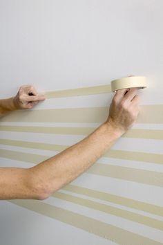 on fixe des bandes de ruban de masquage au mur pour bien définir les rayures horizontales à suivre