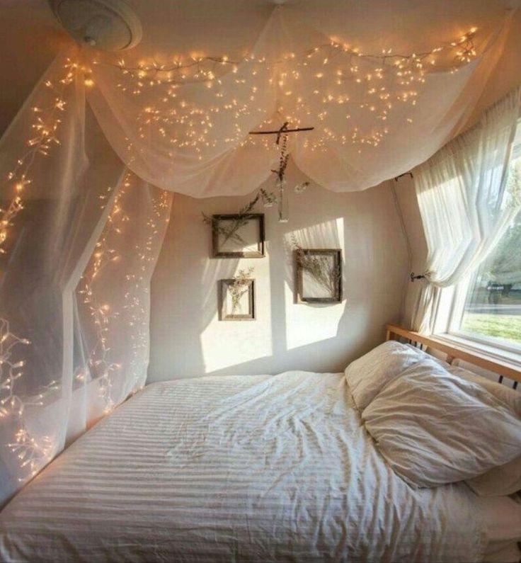 chambre adulte de style bohème avec un ciel de lit en tulle et des guirlandes…
