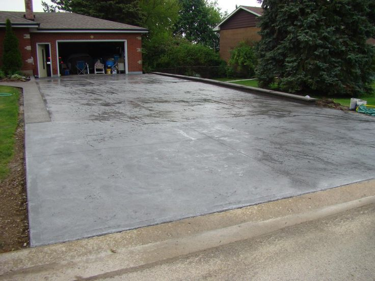 Grey coloured textured concrete driveway looks awesome and will last for years adding value to this home.