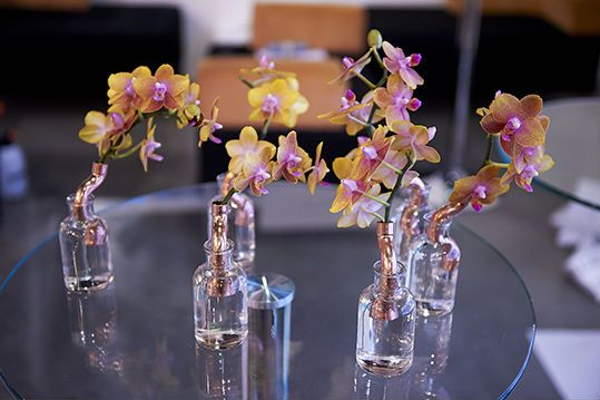 Baby orchids styled with glass bottles and copper fittings