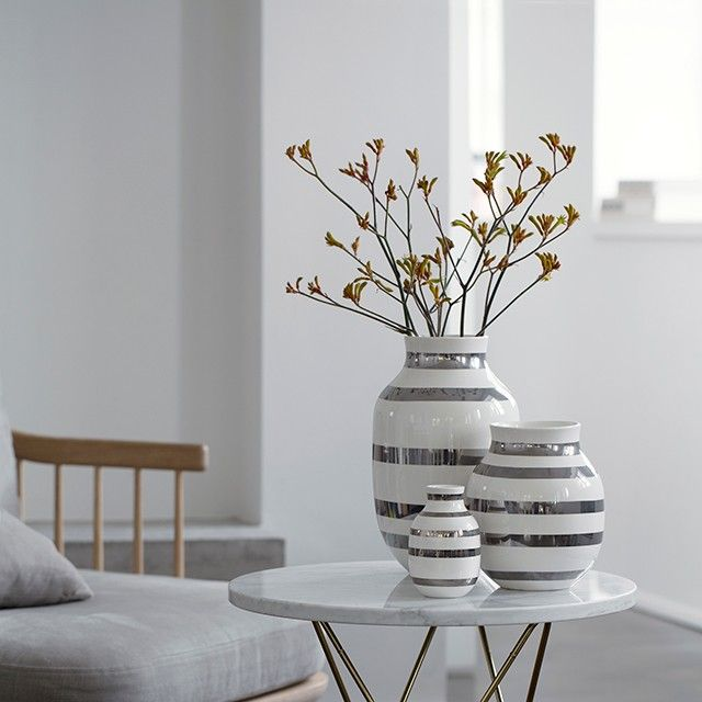 Kähler's beloved design is immortalised in two of the hottest materials, metal and ceramic. This popular vase size goes perfectly with all flowers of the season, and the beautiful silver stripes make a fantastic backdrop for the coloured bouquets.