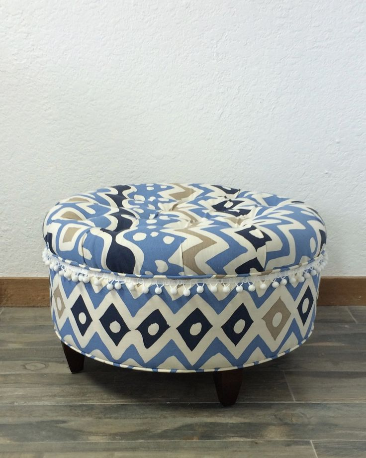 """Upholstered Ottoman, Blue Ottoman, Upholstered Stool, Tufted Ottoman, Alan Campbell, China Seas, Quadrille Fabric, Cap Ferrat. Classic tufted ottoman in a bold graphic tribal print fabric. Upholstered in Alan Campbell/Quadrille Fabrics """"Cap Ferrat"""" Multi Blues on Tint with a color palette of blue, navy blue, white and khaki. Pom Pom trim is added for a touch of playful whimsy. Fabric content is linen/cotton blend. Ottoman's four (4) legs have dark walnut finish. Great for a family room or..."""