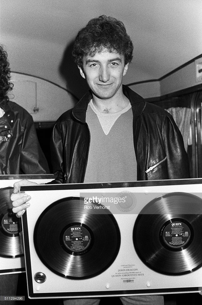John Deacon of Queen holding up a gold disc on board a train (De Kameel) from Leiden to Amsterdam, Netherlands, after a gig at Groenoordhal, Leiden, 25th April 1982. photo by Rob Verhorst
