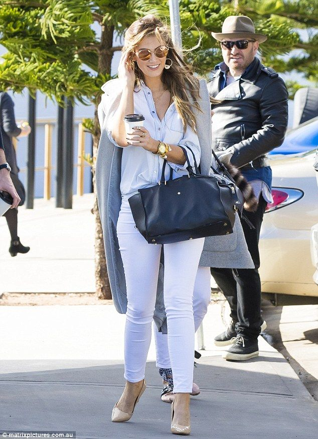Gone with the wind! Delta Goodrem fails to tame her luscious locks in the strong breeze ahead of boarding a yacht with her Voice team and friends