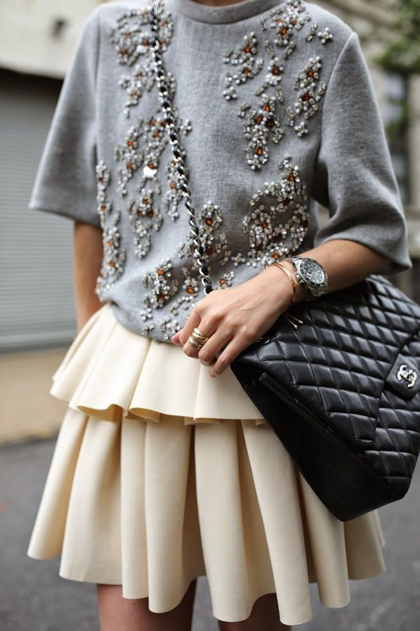 An embellished sweater is worn with a peplum skirt and Chanel bag