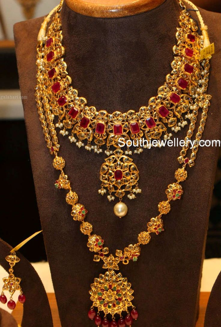 Featuring bridal pachi necklace set from Manepally Jewellers. A broad pachi work necklace studded with square shaped rubies and uncut diamonds with small basara pearls hanging along its bottom. A long pachi work haram with alternating floral and ball clasps and attached flower pendant studded with uncut diamonds, rubies and emeralds.