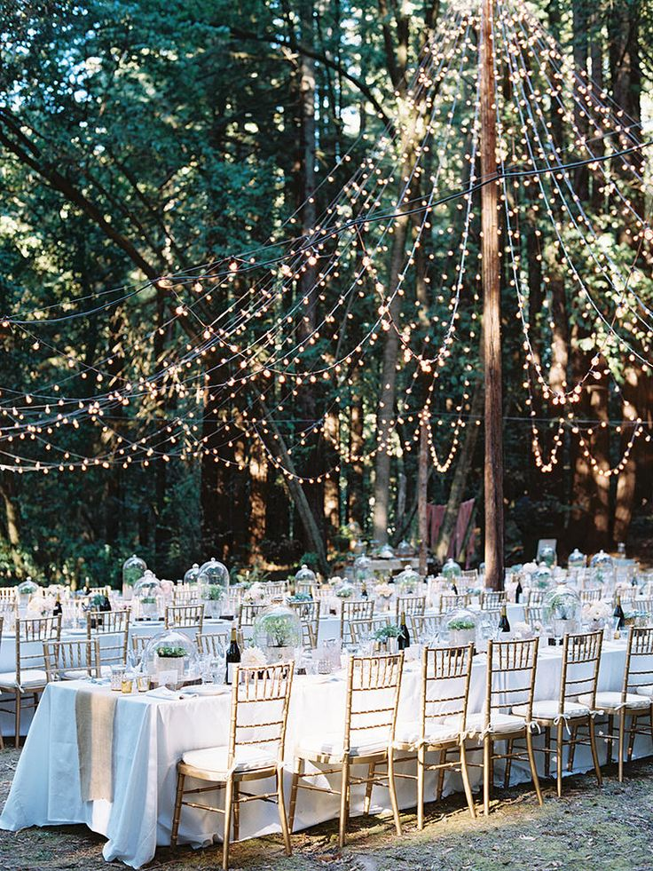 Want a woodland wedding? Set the outdoor reception aglow with a DIY string light tent for magical mood lighting.