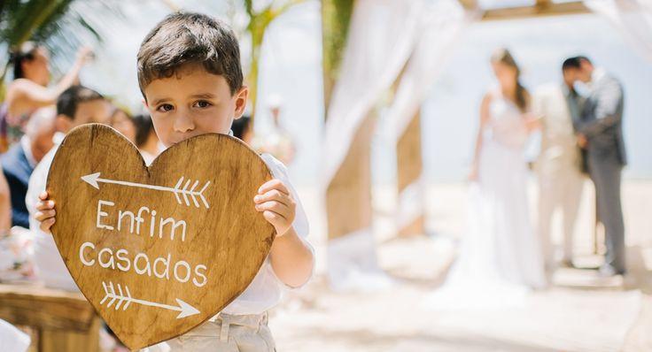 """Pajem fofo com plaquinha de """"Enfim Casados"""" com formato de coração nesta cerimônia na casamento na praia. Tem mais detalhes desta cerimônia ao ar livre em Trancoso no site! (Foto: The Kreulichs) #noivinho #placa #criança #kid"""