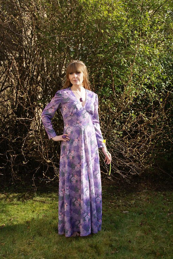 A beautiful Vintage 70s Maxi Dress. In a lilac purple shade with floral patterns of green and pink, this dress has a v-neck and long sleeves. Very pretty Spring dress in good vintage condition. Measurements: Pit to Pit (laid flat): 17 Waist: 30 Length: 55.5 This would best fit a UK