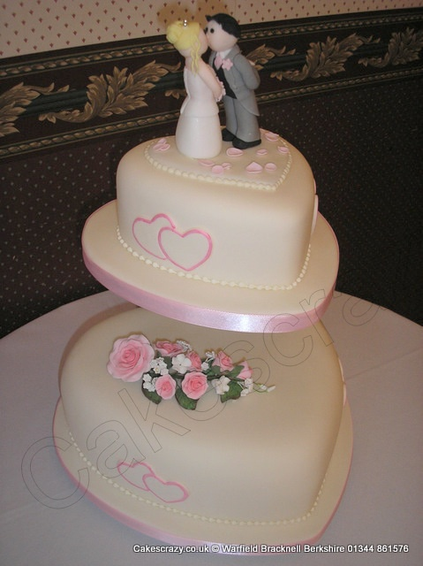 Two tier heart shaped wedding cake covered in ivory icing with pink hearts and piped bead detail and pink sugar roses. Topped with a sugar modelled wedding couple and groom leaning into the bride