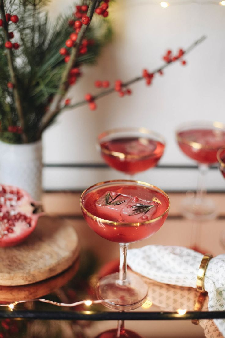 Pomegranate Poinsettia cocktail recipe for Christmas. made with cranberry, pomegranate juice, champagne, vodka, and fancy ice cubes made of berries and rosemary!