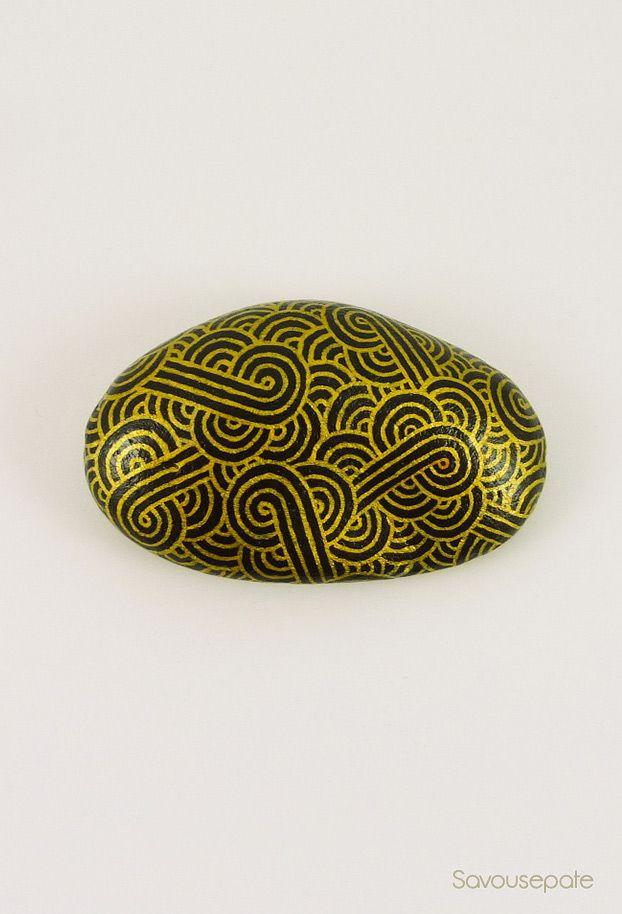 Galet peint noir aux volutes jaunes dor es galet for Galet decoratif noir