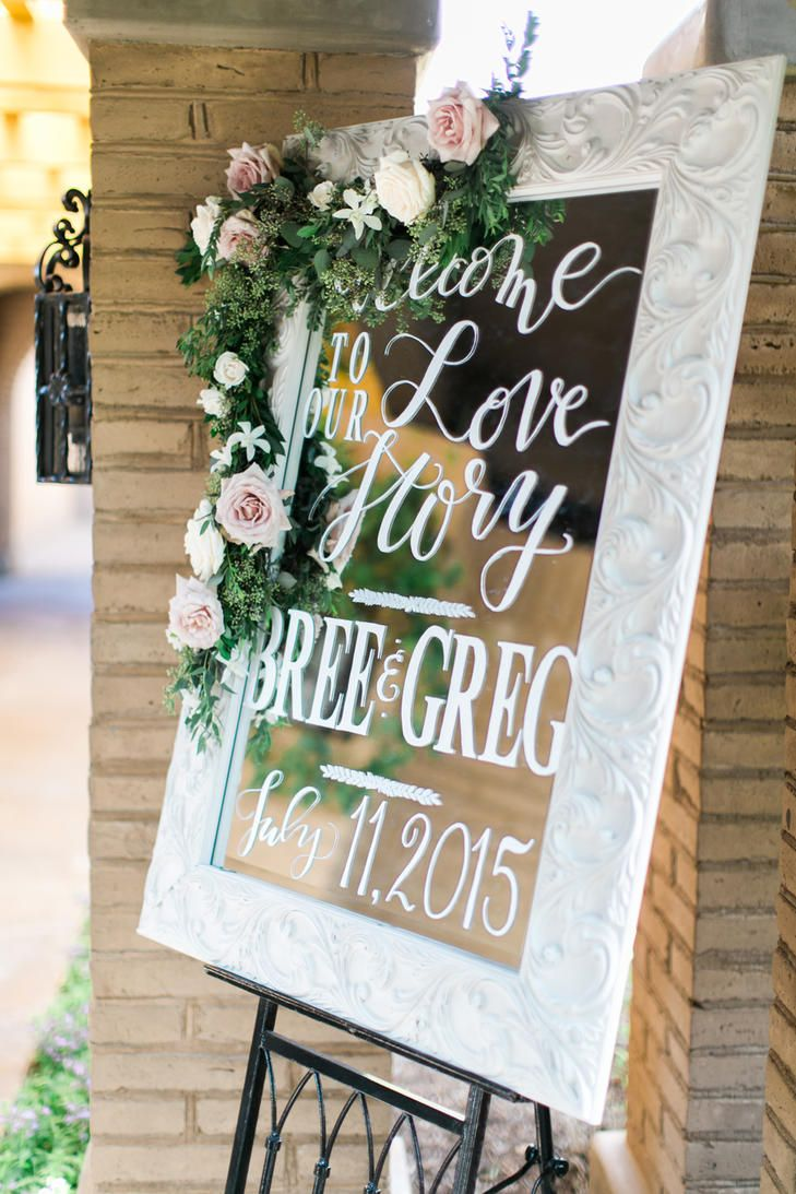 Elegantly framed mirrors decorated with blush roses and greenery scattered throughout the wedding ceremony and reception.