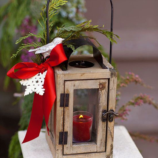 Use what you have decor: a lantern turns Christmas decoration when you add some greens and a sparkly snowflake tied on with a red satin ribbon. A red candle inside give off a welcome glow.