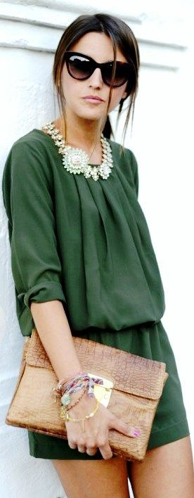 Statement gold necklace, green jumpsuit and braun clutch with black sunglasses.