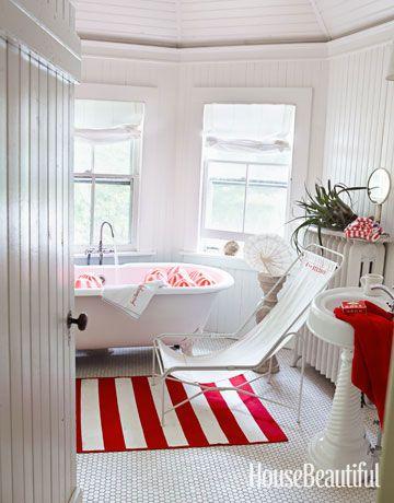 In questo bagno tutto bianco, un tappeto rosso a righe conferisce allo spazio un punto focale in grassetto e illumina tutto.  consulente di design Ellen O'Neill ha aggiunto dettagli e accessori in tutta la casa Bridgehampton, New York - come questa sedia imbragatura tela - di mantenere una atmosfera casual.