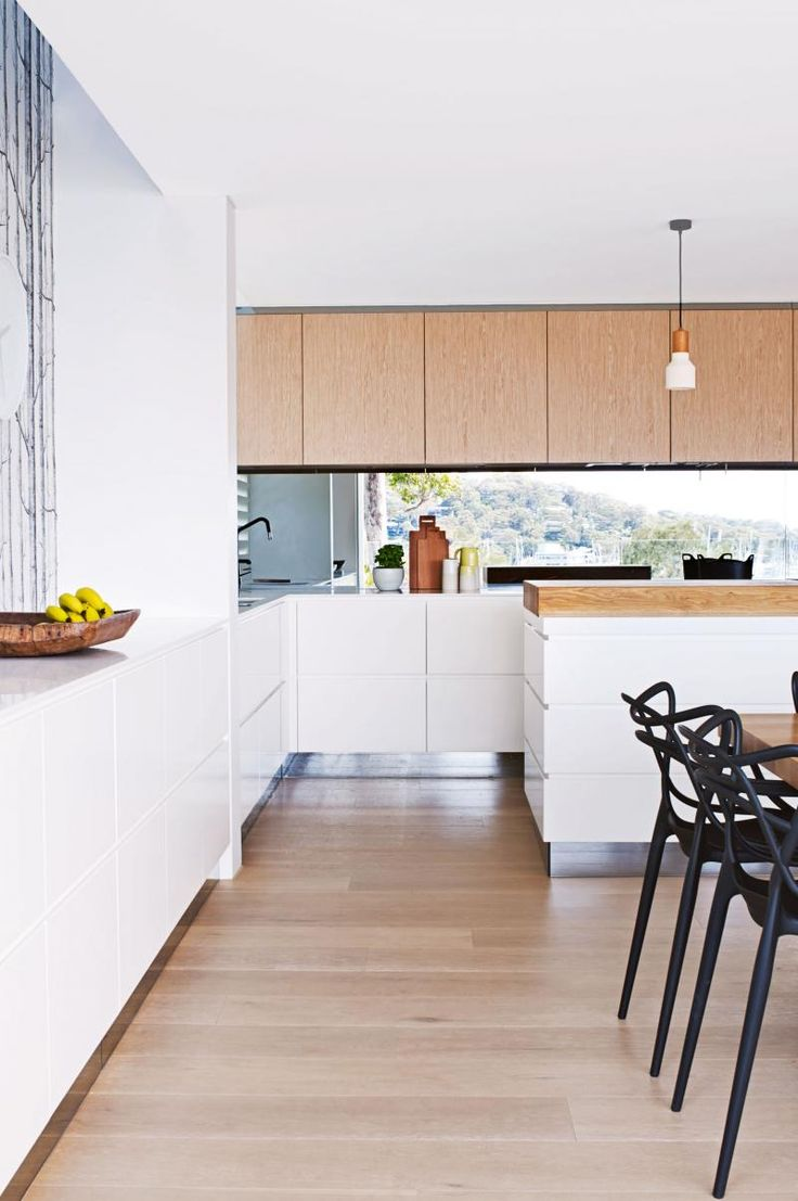 Jan-15-Thrum-home-pittwater-kitchen-floorboards-timber-cupboards-white-cabinetry-black-chairs