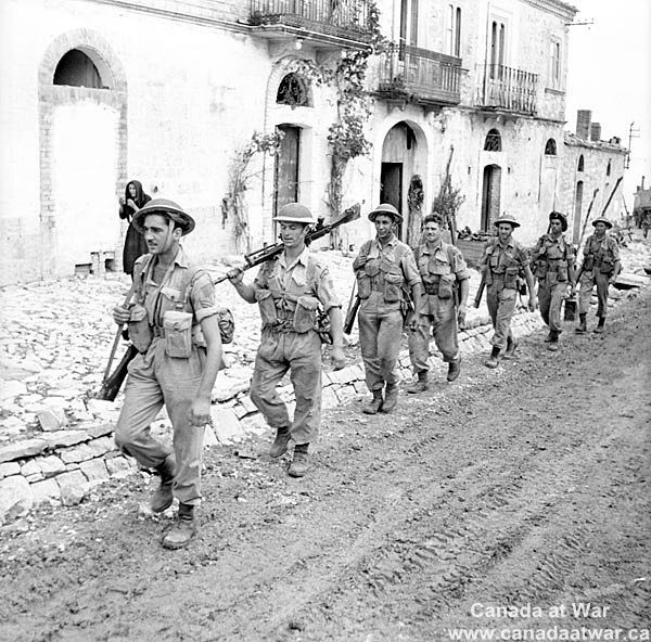 Italy (Misc.) - Infantrymen of the Hastings and Prince Edward Regiment advancing through Motta. October 2, 1943, Motta, Italy.