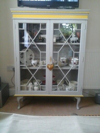 """Glass front display cabinet, with reclaimed queen anne legs from our old otoman, found the cabinet in a charity shop for £15! Was stained and badly scratched. Painted it in """"Misty mountain"""" with """"Bumblebee"""" accents, hey presto, tv stand and displays granny's china and other nick-nacks perfectly."""