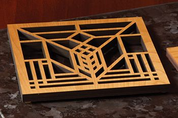 Lake Geneva Tulip Trivet; Multi-ply wood trivet with the stylized tulip design Wright created for the art glass windows in the now demolished Lake Geneva Hotel (Lake Geneva, Wisconsin, 1911). $24.00