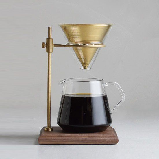 Brew your morning cup with this brass & walnut pour-over coffee set. This brewer stand set is perfect for those who want to indulge in a deeper, richer coffee experience. It comes with a stand, filter, brewer, server, and holder. The brewer stand is made from walnut wood with a brass stand and ring that …