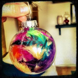 clear glass ornament filled with feathers