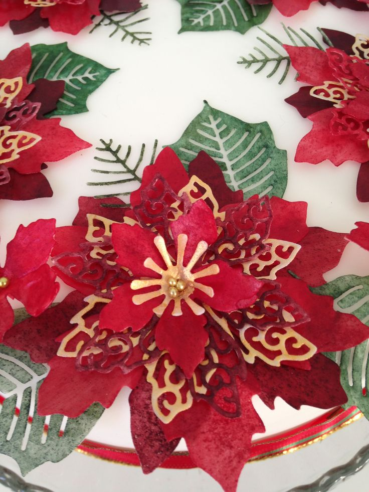 Close up of a die cut poinsettia flower that has been attached to a Christmas cake. All 100% edible, this flower has been made using wafer paper. Tiny edible pearls have been used to decorate the centre of the flower and has been surrounded by leaves and ferns.